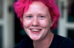 Smiling woman with short pink hair
