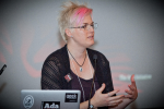 CC BY-SA Adam Novak. Woman with pink hair speaking and gesturing