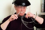 A women wearing a face shield and holding jewelry wire and tools