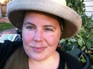 A woman smiling wearing a gardening hat