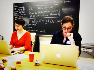 Ada Lovelace Day wikiathon: two women work on laptops in front of a blackboard with wikiathon instructions