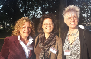 Three women squinting into the sun