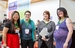 Four women standing at a conference and smiling, CC BY-SA Jenna Saint Martin Photo