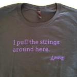 "Grey shirt with purple text reading ""I pull the strings around here. Puppet Labs"""