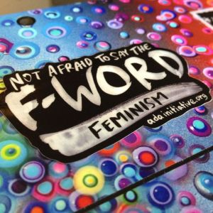 "Sticker reading ""Not afraid to say the F-WORD: FEMINISM adainitiative.org"" on a colorful laptop skin"