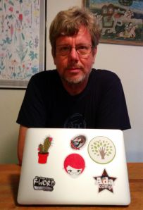 Man sitting behind a laptop covered in colorful stickers