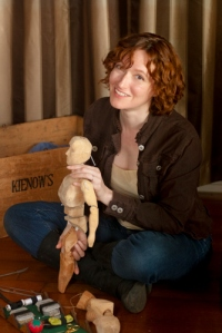 Smiling woman sitting cross-legged holding a wooden puppet