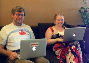 Two people sitting on a couch with laptops, one with a PyLadies sticker