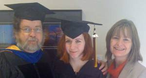 One man and two women, two of them wearing mortarboards