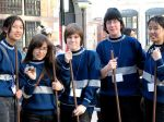 5 teenagers dressed in Slytherin costumes and holding quiddich equipment