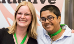 Two women smiling wearing green badge lanyards