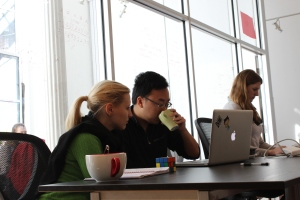 Photograph of Hacker School participants pair-programming and drinking coffee