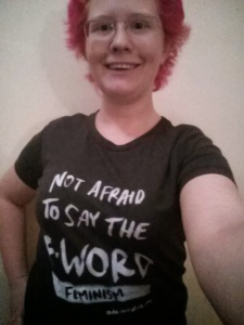 "Someone with pink hair wearing a ""Not afraid to say the F-word: Feminism!"" shirt"